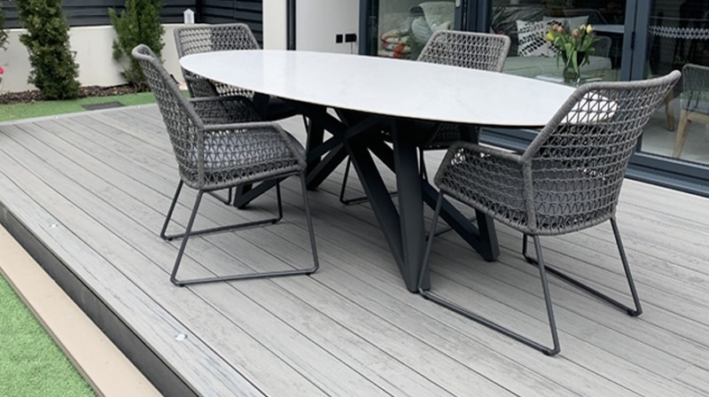 Grey deck in back garden with dining set